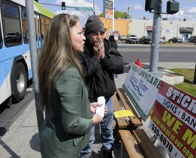 "Mayor Mary Verner holds a press conference at the corner of Indiana Avenue and Monroe Street on Monday to announce that bus benches with signs will be removed. Bus rider Dave Parisia, right, told her removing the benches would be a ""waste of money.""  (Dan Pelle / The Spokesman-Review)"