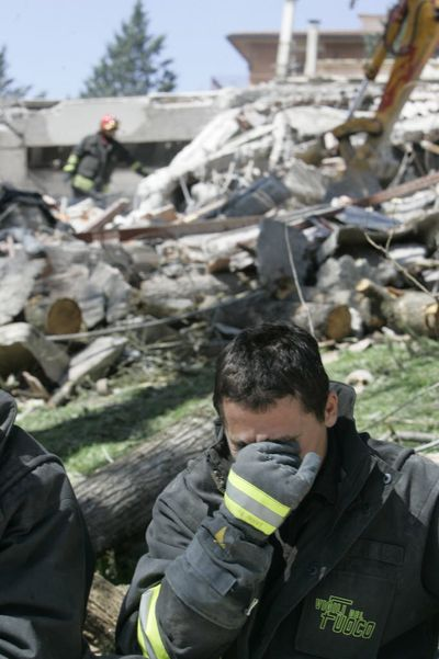 A firefighter reacts as he stands next to the site where a four-story building collapsed following a earthquake in L'Aquila, central Italy, on April 6, 2009. A powerful earthquake in mountainous central Italy knocked down blocks of buildings early Monday as residents slept, killing at least 50 people and trapping many more, officials said. Interior Minister Roberto Maroni, arriving in L'Aquila hours after the quake, said at least 50 people had been killed and that the toll was likely to rise as rescue crews clawed through the debris of fallen homes. L'Aquila is the capital of the Abruzzo region and lies in a valley surrounded by the Apennine mountains. (Associated Press)
