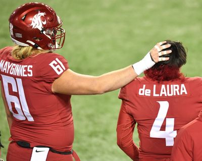 Washington State offensive lineman Hunter Mayginnes pats quarterback Jayden de Laura on the head after the Cougars fell to Oregon in last Saturday's Pac-12 game at Martin Stadium in Pullman.  (Tyler Tjomsland/THE SPOKESMAN-RE)