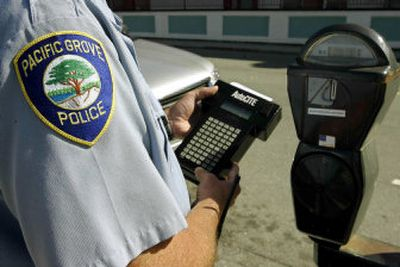Officer Tony Marino demonstrates a handheld computer used to write parking tickets in Pacific Grove, Calif.   (Associated Press / The Spokesman-Review)