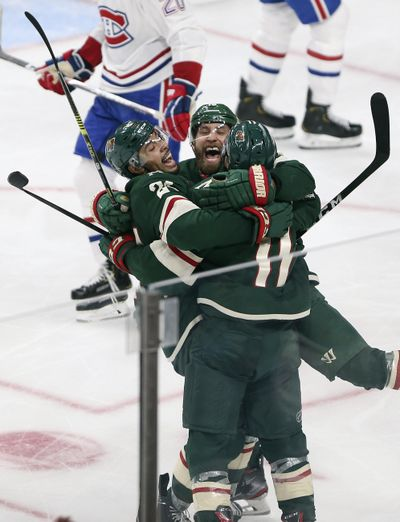 Minnesota Wild's Zach Parise, right, celebrates with teammates Jason Zucker, center, and Matt Dumba, right, after scoring a goal against the Montreal Canadiens in the third period of an NHL hockey game Sunday Oct. 20, 2019, in St. Paul, Minn. (Stacy Bengs / Associated Press)