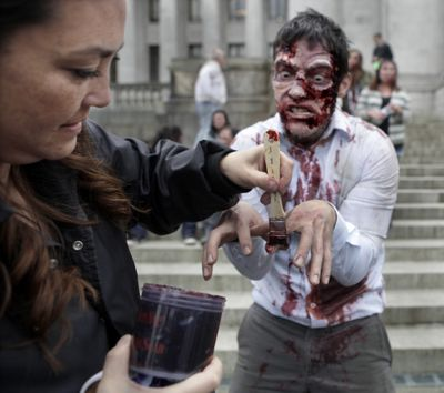 """Actor David S. Hogan gets prepped for his role by makeup artist Akemi Hart on the filming set inspired by the Syfy Network series """"Z-Nation"""" on the Capitol grounds in Olympia on Tuesday. (Associated Press)"""