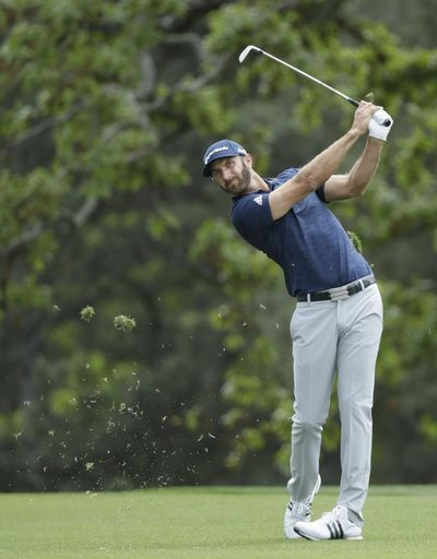 In this April 8, 2018 file photo Dustin Johnson hits a shot to the first hole during the fourth round at the Masters golf tournament in Augusta, Ga. Johnson has been No. 1 for 15 months and needs his best finish at The Players Championship to have a chance to stay there. (David J. Phillip / Associated Press)