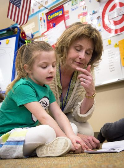 Mullan Road Elementary kindergarten teacher Marce Hagood works with Olivia Green on a reading assignment on Thursday, March 17, 2016. Kindergarten students at Mullan Road will be bused to nearby Moran Prairie next year as Mullan Road is expanded. The arrangement has bothered some parents and is an indicator of the wider efforts the Spokane district is making to accommodate new smaller class-size mandates, which will require about 120 new classrooms. (Colin Mulvany / The Spokesman-Review)