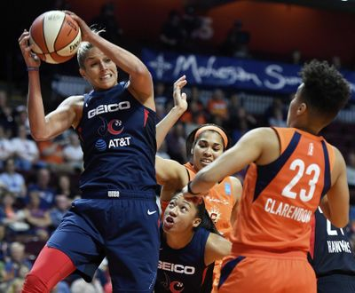 In this June 11, 2019 photo, Washington Mystics forward Elena Delle Donne pulls down a rebound next to Connecticut Sun guard Layshia Clarendon during a WNBA basketball game in Uncasville, Conn. (Sean D. Elliot / The Day via AP)