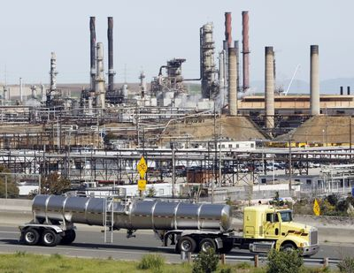 A tanker truck drives by the Chevron oil refinery in Richmond, Calif., on Tuesday. Chevron Corp. says it will cut 2,000 jobs this year and will continue reducing its work force through 2011. (Associated Press)