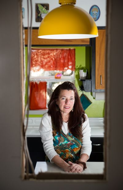 """Artist and educator Carrie Scozzaro could now add """"successful home renovator"""" to her list of titles. Here she is seen on March 17 in her transformed Spokane Valley home that she has dubbed The Fortress.  (Libby Kamrowski/The Spokesman-Review)"""