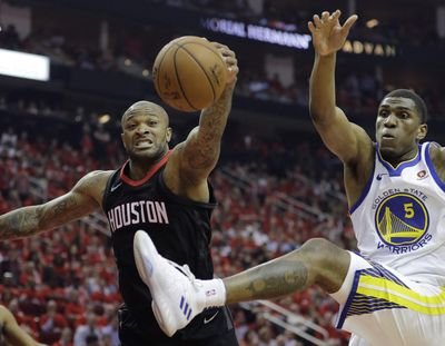 Houston forward P.J. Tucker, left, and Golden State forward Kevon Looney chase a rebound during the first half in Game 2 of the NBA Western Conference Finals on Wednesday in Houston. (David J. Phillip / AP)