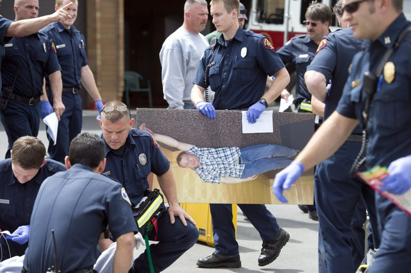 Spokane Valley firefighter Paul Turcotte carries an enlarged photograph that represents a shooting victim as rescue crews participate in a mass casualty training exercise Wednesday at the department's old administration building. (Dan Pelle)