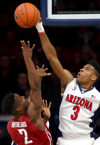Arizona guard Justin Simon  blocks a shot by Washington State guard Ike Iroegbu during Saturday's Pac-12 game. (Kelly Presnell / Arizona Daily Star)
