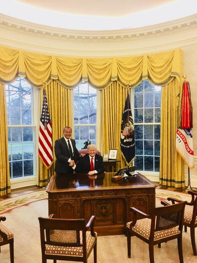 """This image from the website of Allied Wallet CEO Ahmad """"Andy"""" Khawaja shows Khawaja posing with President Donald Trump in the Oval Office of the White House in Washington. Khawaja gave more than $4 million to Hillary Clinton's failed presidential campaign and other Democrats, then began extending his largesse to Republicans after a lunch with GOP fundraiser Elliott Broidy two weeks after Trump clinched the presidency. Records obtained by the Associated Press show that Khawaja has helped pornographers, payday loan debt collectors and offshore gambling operations get past the gates of the banking system. (Associated Press)"""