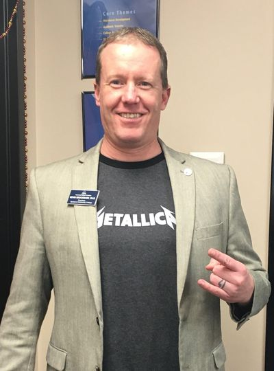 Spokane Community College President Kevin Brockbank wears a Metallica t-shirt under his suit jacket to work on Tuesday. SCC got a $100,000 grant from the band's foundation. (Spokane Community College)