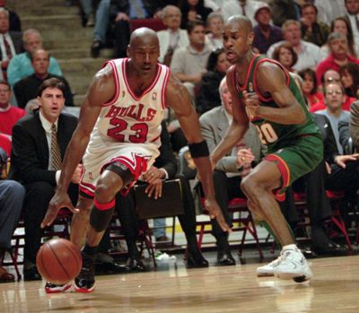 Chicago Bulls' Michael Jordan drives around Seattle SuperSonics' Gary Payton during Game 1 of the NBA Finals June 5, 1996, in Chicago. The Bulls won 107-90 and the much-anticipated matchup of Jordan and Payton in the series opener was well worth the wait. (BETH A. KEISER / ASSOCIATED PRESS)