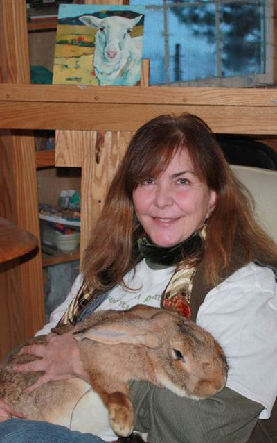 Kit Jagoda poses with a rabbit named Albrecht in her studio in a loft above the bunny barn at her home in the Seven Mile area.