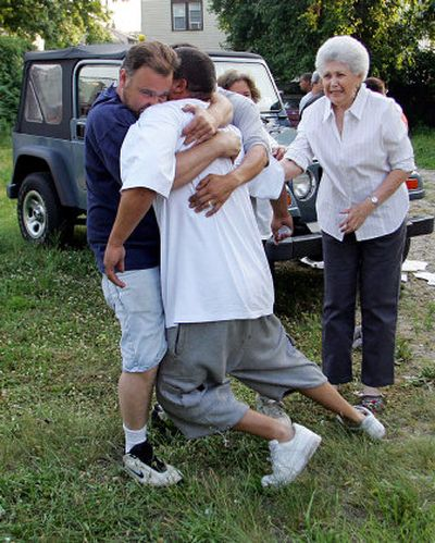 David Agosto, center, father of missing boy Daniel Agosto, collapses in the arms of a friend  after the discovery of the bodies of Jesstin Pagan, 5, Daniel Agosto, 6, and Anibal Cruz, 11. The boys had been missing since Wednesday.   (Associated Press / The Spokesman-Review)