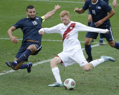 In this 2017 photo, Indiana's Cory Thomas (11) kicks the winning goal past Penn State's Dani Marks (18) during overtime in a Big Ten NCAA college soccer match in Bloomington, Ind. The NCAA Board of Directors is allowing each division of the association to decide independently whether it will be able to conduct championship events safely in fall sports such as soccer, volleyball and lower levels of football during the coronavirus pandemic.  (Associated Press)