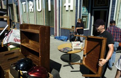 Marty McKinney loads furniture onto a flatbed trailer at the former Truth Ministries building, 238 W. Sprague, Wednesday morning. The homeless shelter's new location won't open until a sprinkler system can be installed.   (The Spokesman-Review)