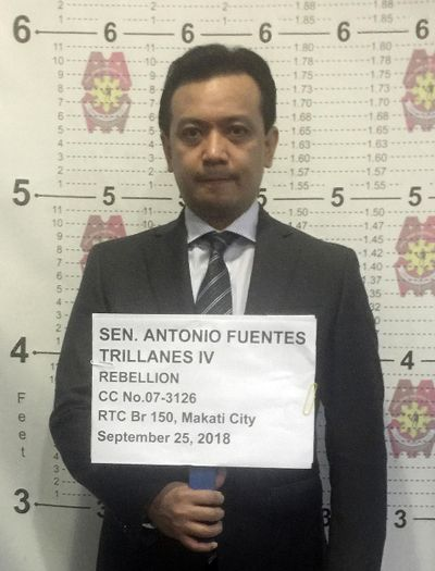 Philippine opposition Sen. Antonio Trillanes IV stands for his mugshot inside a police station in Makati, metropolitan Manila after the Makati Regional Trial Court Branch 150 issued an order for his arrest Tuesday, Sept. 25, 2018. (PHILIPPINE NATIONAL POLICE MAKATI / Associated Press)