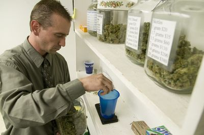 Christopher Stevens, owner of Change, a medical marijuana dispensary in north Spokane, fills an order for a disabled customer. Pictured at top, a customer holds the medical marijuana she purchased for $80.colinm@spokesman.com (Colin Mulvany / The Spokesman-Review)