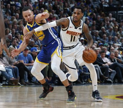 In this Tuesday, Jan. 15, 2019, file photograph, Denver Nuggets guard Monte Morris, right, drives past Golden State Warriors guard Stephen Curry in the second half of an NBA basketball game Tuesday, Jan. 15, 2019, in Denver. (David Zalubowski / Associated Press)