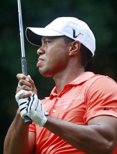 Tiger Woods watches his tee shot on the fourth hole.  (Associated Press / The Spokesman-Review)