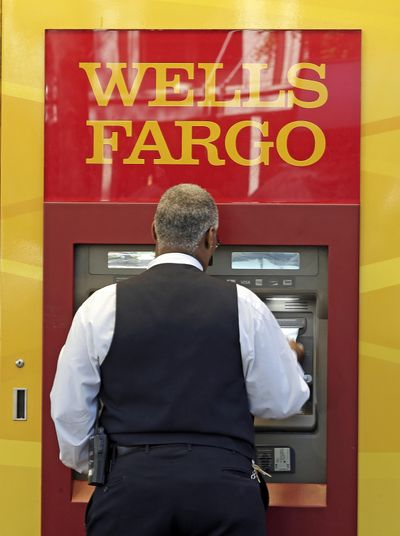 In this Thursday, April 13, 2017, photo, a man uses a Wells Fargo ATM in Charlotte, N.C. Wells Fargo & Co. reports earnings, Friday, July 14, 2017. (Chuck Burton / Associated Press)