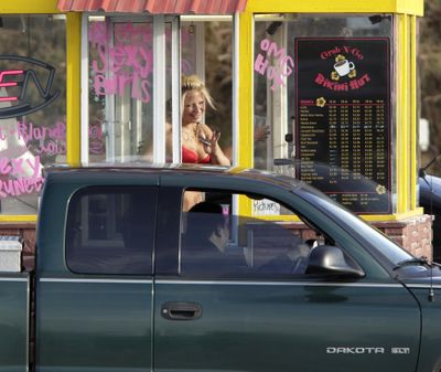 In this Feb. 2, 2010, file photo, a barista at a Grab-N-Go Bikini Hut espresso stand holds money as she waves to a customer, just outside the city limits of Everett, Wash., in Snohomish County. (Ted S. Warren / Associated Press)