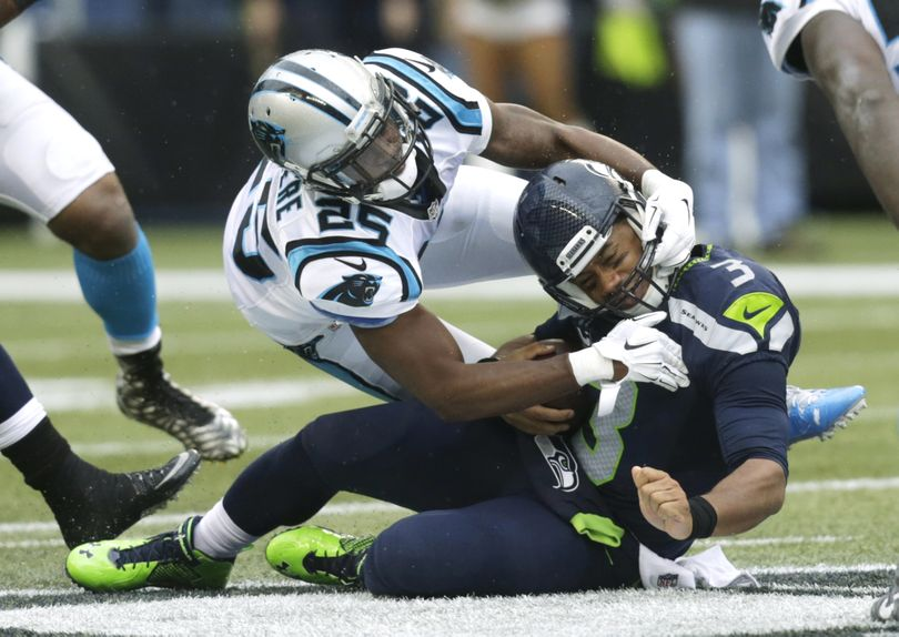 Seattle Seahawks quarterback Russell Wilson, right, is tackled by Carolina Panthers cornerback Bene' Benwikere after Wilson rushed for a gain in the first half of an NFL football game, Sunday, Oct. 18, 2015, in Seattle. (Stephen Brashear / AP)