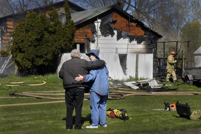 Jean Davenport, right, is comforted by a friend after returning home to find her house, at 16725 E. Valleyway, destroyed by fire Friday.  (CHRISTOPHER ANDERSON / The Spokesman-Review)