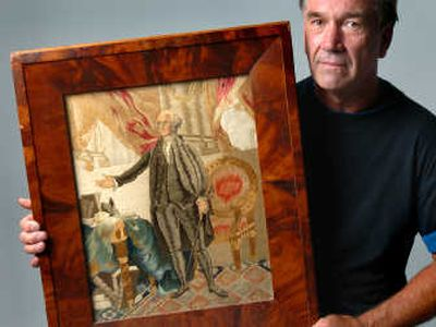 Mike Tracy holds a George Washington needlework piece that he estimates to be from the early 1800s.  (Photos by Ingrid Barrentine/ / The Spokesman-Review)
