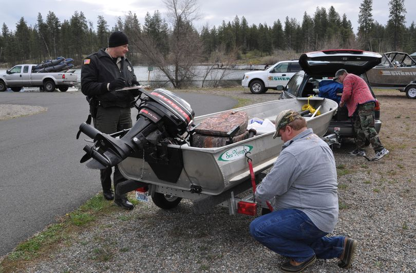 Spokane County Sheriff Deputy Jay Bailey checks the boat of anglers before they launch at West Medical Lake on Saturday. The opening day of the lowland lake fishing season is a good opportunity for the deputies to contact a large number of boaters to be sure their boats are up to snuff. Requirements include: Current registration on board, registration numbers properly shown, boat drivers 35 and under need boater education certificate, life jackets for everyone in the boat and functioning fire extinguisher.  (Rich Landers)