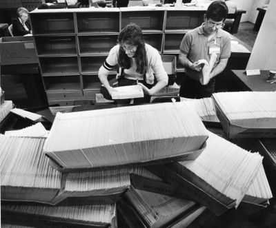 Dale Petrie and Debra Ottosen open some of the 40,000 census forms that arrived at the U.S. Census office in Spokane for the 1990 census. (Colin Mulvany / The Spokesman-Review)