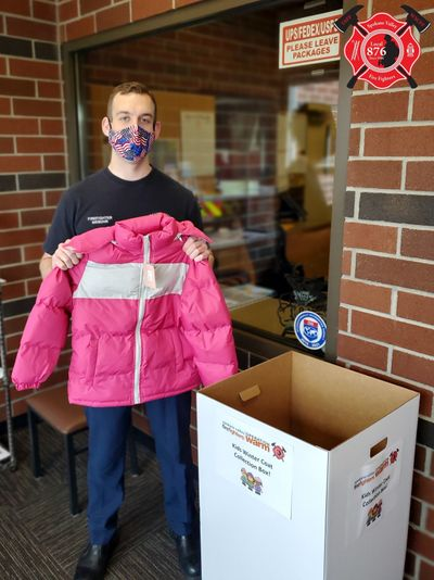 Spokane Valley firefighter Scott Niebuhr displays a child's coat during a coat drive through Operation Warm. Those interested in donating can drop off their donations in a collection bin at any of Spokane Valley Fire Department stations.  (Courtesy)