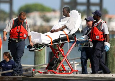 A survivor from a boat that capsized off the coast of Florida is brought into a U.S. Coast Guard Station on Wednesday in Riviera Beach, Fla.  (Associated Press / The Spokesman-Review)