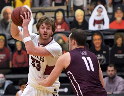 Whitworth forward Reed Brown (33) looks to pass as Puget Sound forward Grant Erickson (11) defends during the first half of a college basketball game, Friday, Feb. 12, 2021, at Whitworth University.  (Colin Mulvany/THE SPOKESMAN-REVIEW)