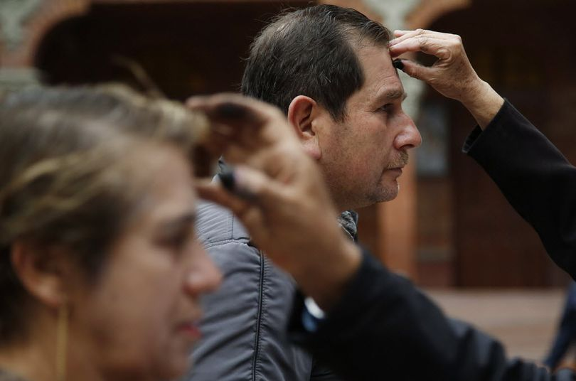 Catholics line up to get their foreheads marked with ashes in the shape of a cross during Ash Wednesday Mass in Bogota, Colombia, Wednesday, Feb. 10, 2016. Ash Wednesday for Catholics worldwide ushers in a period of penitence and reflection, known as the season of Lent, that leads up to Easter Sunday. (AP Photo/Fernando Vergara)