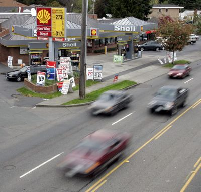 """Cars whiz past a gas station Monday, Oct. 17, 2005, in Seattle. The Washington State Transportation Commission is hoping to enlist drivers from across the state to experiment with a per-mile """"road user charge,"""" part of a pilot study on the feasibility of replacing the state gas tax with the user charge. (TED S. WARREN / AP)"""
