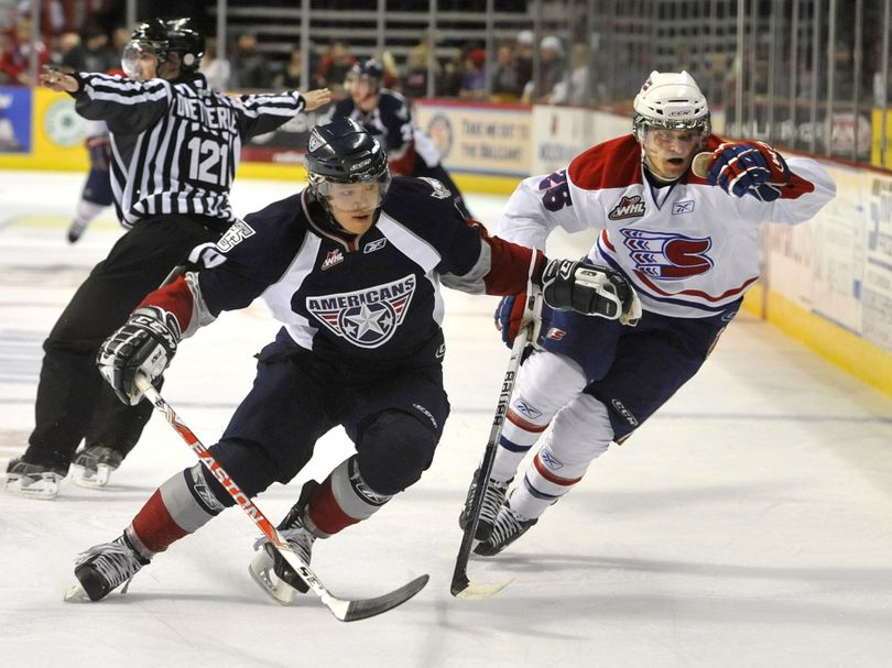 Chiefs Dominik Uher and Tri-City Zachary Yuen chase down the puck along the boards in the first period on Jan 29, 2011, in the Spokane Arena. (Dan Pelle / The Spokesman-Review)