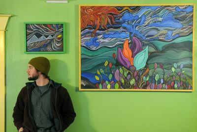 """Artist Max Brown with his abstract paintings, """"Egyptian Sun"""" and """"Quest for the Top,"""" at his home in north Spokane. (Dan Pelle / The Spokesman-Review)"""