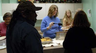 Janet Single-Schwall, center, along with her daughter Rachael, 13, serve lunch at First Presbyterian Church Ecumenical Food Kitchen on Jan. 31.   (Kathy Plonka / The Spokesman-Review)