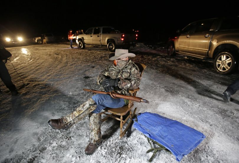 Arizona rancher LaVoy Finicum holds a rifle as he guards the Malheur National Wildlife Refuge on Tuesday near Burns, Ore.