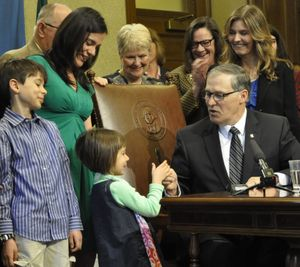 OLYMPIA --  Gov. Jay Inslee hands the official signing pen to Zoe Adler, 5, of Seattle, while her brother Jake, age 9, looks on after Inslee signed a bill requiring medical professionals to complete training in suicide assessment, treatment and prevention. Their father, Matt Adler died as a result of suicide and their mother Jennifer Stuber, standing behind Jake, is the director of Forefront innovations in suicide prevention and lobbied strongly for the bill.  (Jim Camden)