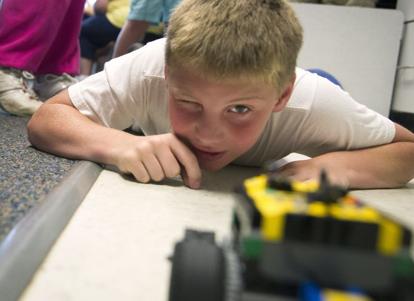 Broadway Elementary summer school student Connor Dehn, 9, keeps an eye on his computer-programmed Lego car as it heads to a target Thursday. (Colin Mulvany)