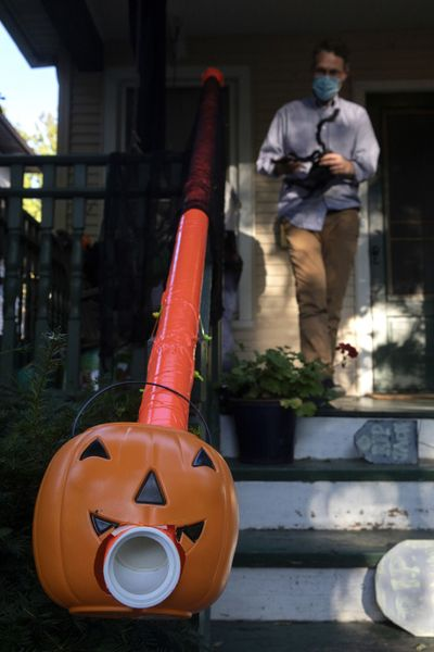 Liam Ford decorates his porch and Halloween treat chute. He was able to use pipe he found in his garage, plus orange duct tape and zip ties to create a candy-delivery system that allows for social distancing.  (Erin Hooley/Chicago Tribune)