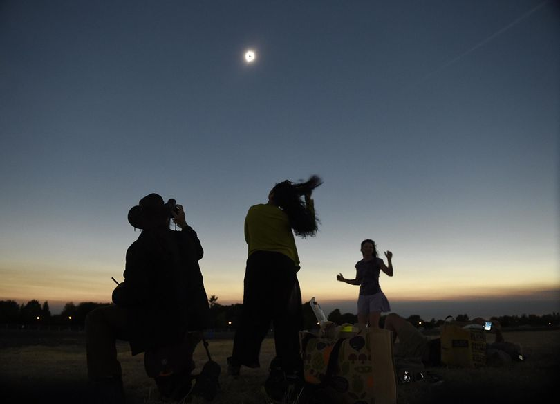 Julian Ledger, of Los Angeles, photographs the solar eclipse while his wife Shayde Ledger and friend Annemarie Penny, right dance during totality at the Albany Regional Airport in Albany, Ore., Monday, Aug. 21, 2017. (Mark Ylen / Associated Press)