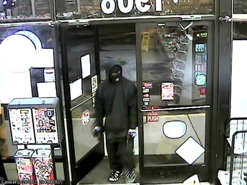 Spokane police today released surveillance photos of a robbery last week at a Browne's Addition convenience store in hopes someone will recognize the gunman. The robbery was reported about 11:49 p.m. Feb. 29 at the Sunset Grocery, 1908 W. Sunset Blvd. The gunman is described as 20 to 22 years old, 5-foot-5 to 5-foot-7 and 150 to 160 pounds. He wore a black knit ski mask, dark hooded sweatshirt, black coat, dark loose pants and black and white athletic shoes. The gun is described as a black semi-automatic pistol.  (survellience)