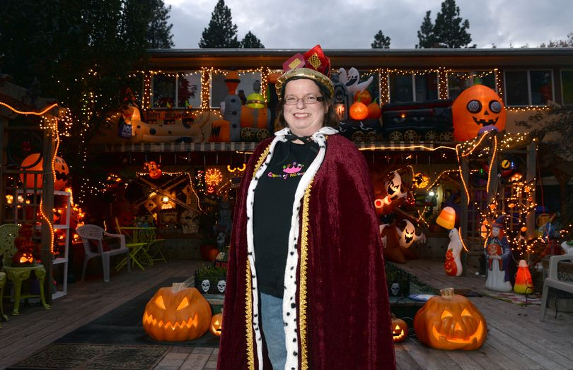 """Chris Sheppard dons only one costume on Halloween, a robe, crown and sweatshirt reading """"Queen of Halloween."""" Indeed, her house dominates the neighborhood, with hundreds of whimsical items for the holiday. Sheppard is shown at her home, 1722 S. Bettman Road in Spokane Valley, on Wednesday. (Jesse Tinsley)"""