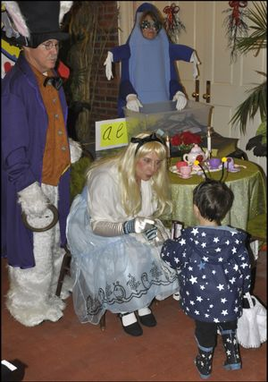 OLYMPIA -- Gov. Chris Gregoire, dressed as Alice in Wonderland, with husband Mike dressed as the White Rabbit, greets 2 1/2 year old Jack Kesler of Olympia Halloween night at the governor's mansion. (Jim Camden)