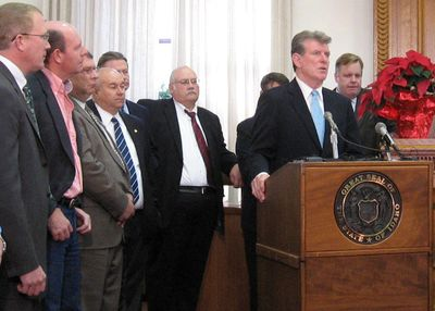 Flanked by legislators and state officials, Gov. Butch Otter announces more state budget cuts Monday in Boise. The only exception will be for public schools.  (BETSY Z. RUSSELL / The Spokesman-Review)