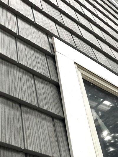 The flat white trim next to the window has a pre-cut groove in it that laps over the vinyl siding. (Tim Carter)